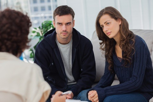 Couple sitting on couch listening to therapist