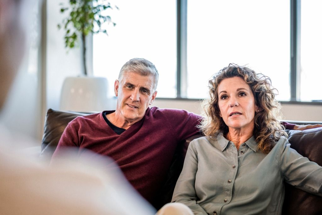 mature couple looking at psychiatrist in office