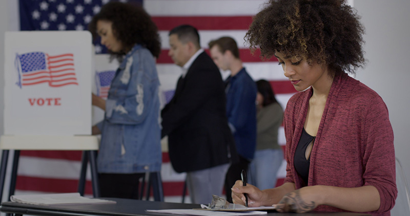 woman filling out voting ballot