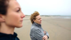 two women on a beach, frowning as they look at the ocean
